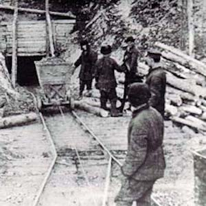 Photograph of a cart full of ore being pulled out of a mine with six prisoners