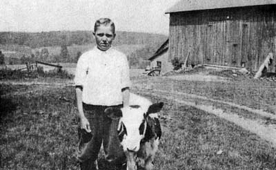 Picture of an orphan child on a barn with his goat.
