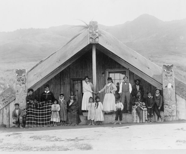 thumbnail of  a Maori men, women, and children arranged for a group portrait on the porch of a whare or wharenui (meeting house) in New Zealand