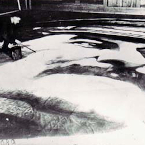 Black and white photograph of prisoner artist painting a large portrait of Stalin