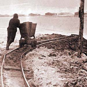 Black and white photograph of a lone prisoner pushing an ore car