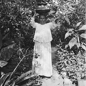 A woman is carrying something on her head