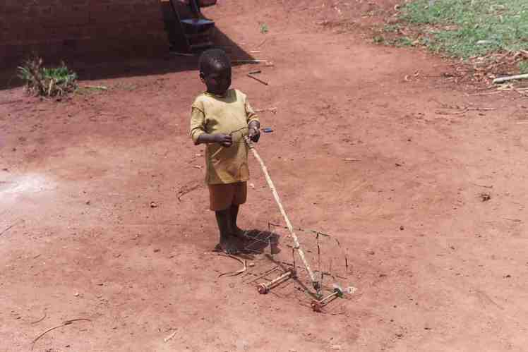 Photo of a boy playing with a wire truck